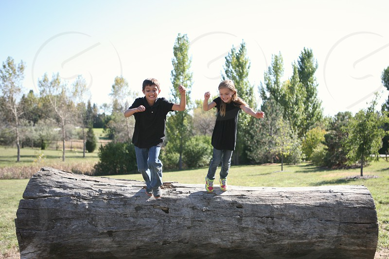 kids jumping playing siblings brother sister outside outdoors backyard fun happy  photo