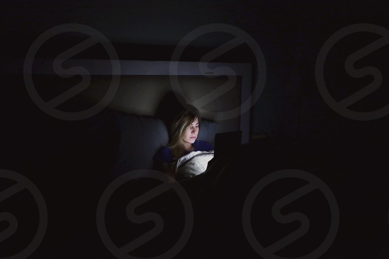 woman sitting on bed using tablet photo