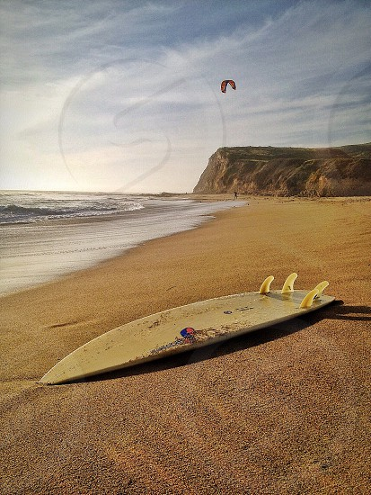 white wooden surf board at sea shore photo