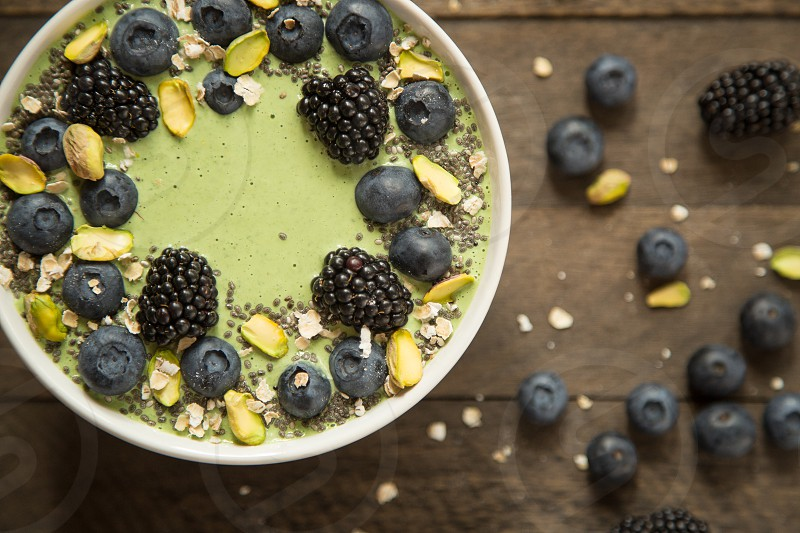 Organic Smoothie Bowl with Kale Coconut Milk Oats Blackberries Blueberries Chia and Pistachios photo