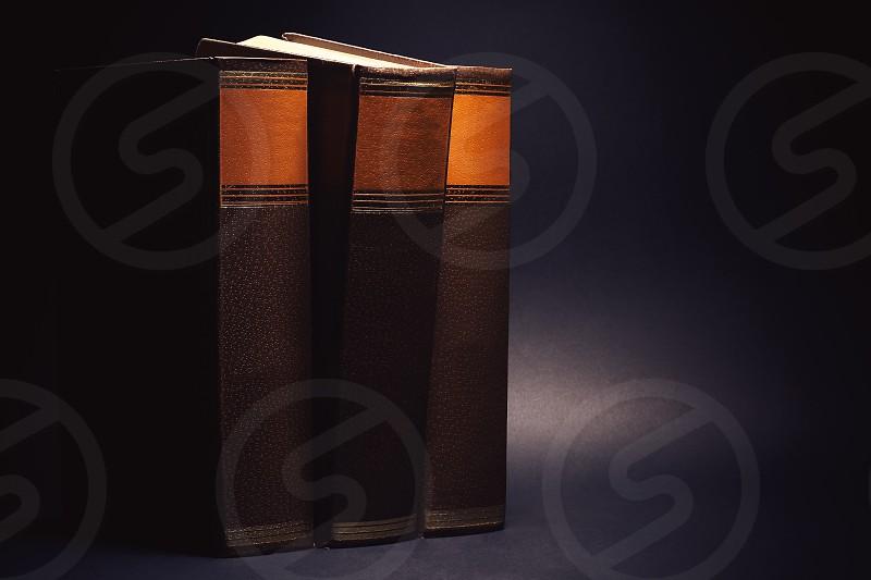 Three old book on black background.  photo