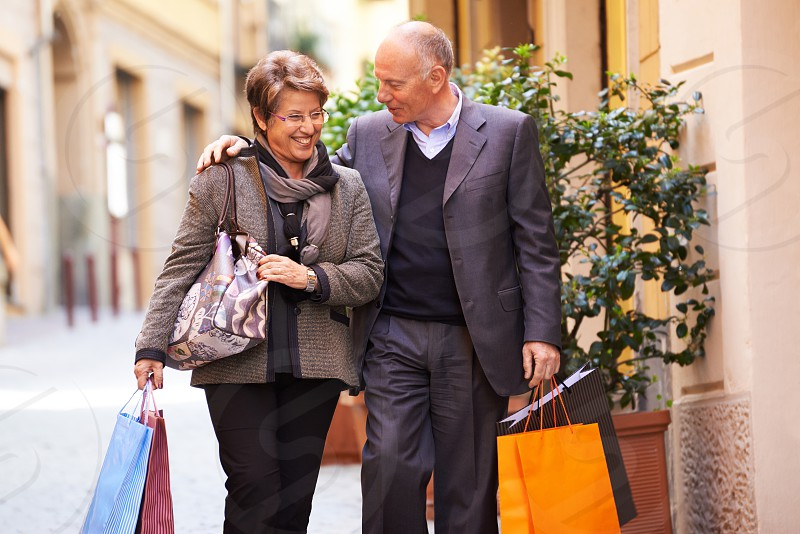 senior; shop; shopping; bags; buy; buyer; 60s; active; activity; bag; carefree; caucasian; cheerful; city; consumer; consumerism; couple; customer; elderly; enjoy; europe; female; fun; happy; hugging; husband; italy; italian; leisure; lifestyle; love; loving; male; man; old; outdoor; people; persons; sale; seniors; shop; smile; smiling; store; street; two; urban; walking; wife; woman photo