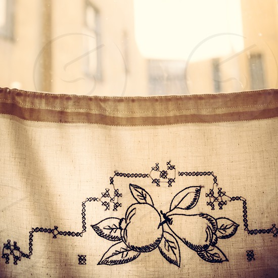 Backlit window with vintage half-curtain with embroidery photo