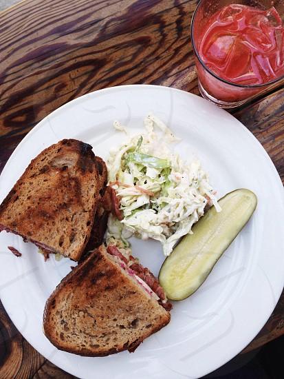 Reuben sandwich with coleslaw & a pickle. photo