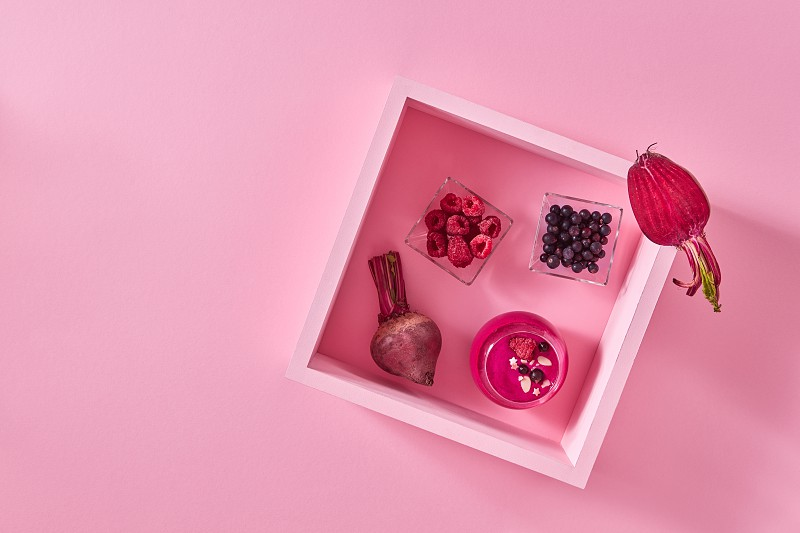 Beetroot berry smoothies in a glass. Food composition with a wooden frame with a glass of smoothies a plate with raspberries and currants on a pink paper background with copy space. Top view photo