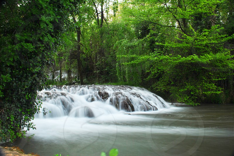 waterfall running over a river rock bed surrounded by green trees photo