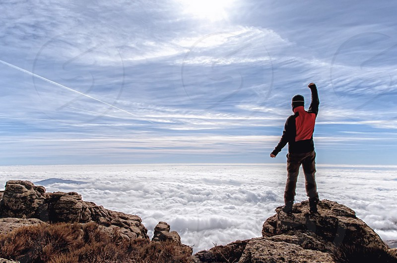 Man on top of mountain under a sea of clouds photo