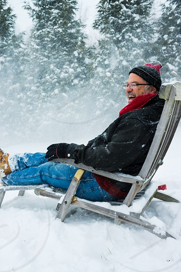 Older male sitting in a deck chair in the snow enjoying a beverage. photo