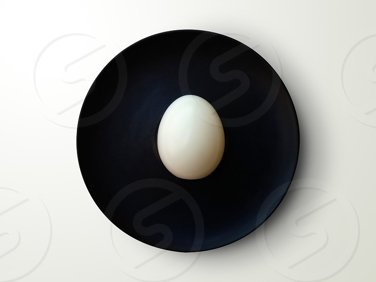 One egg on small black kitchen plate photo