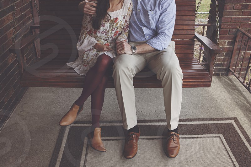 couple engaged engagement legs crossed swing porch love photo