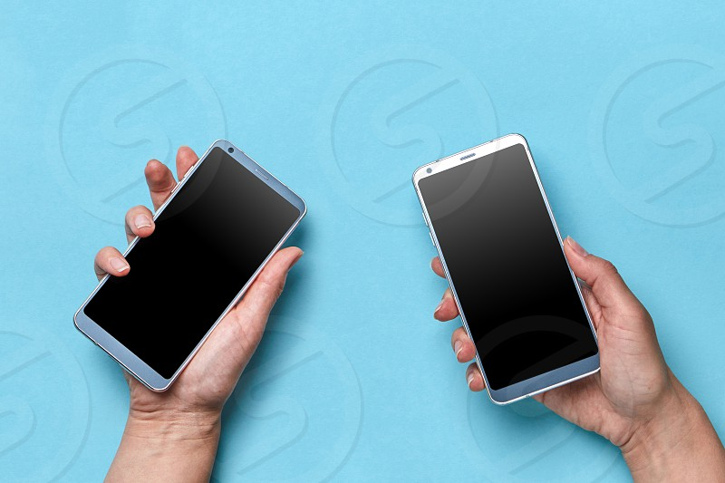 The hand of the girl and the man hold modern mobile phones on a blue background with copy space for text. Flat lay photo