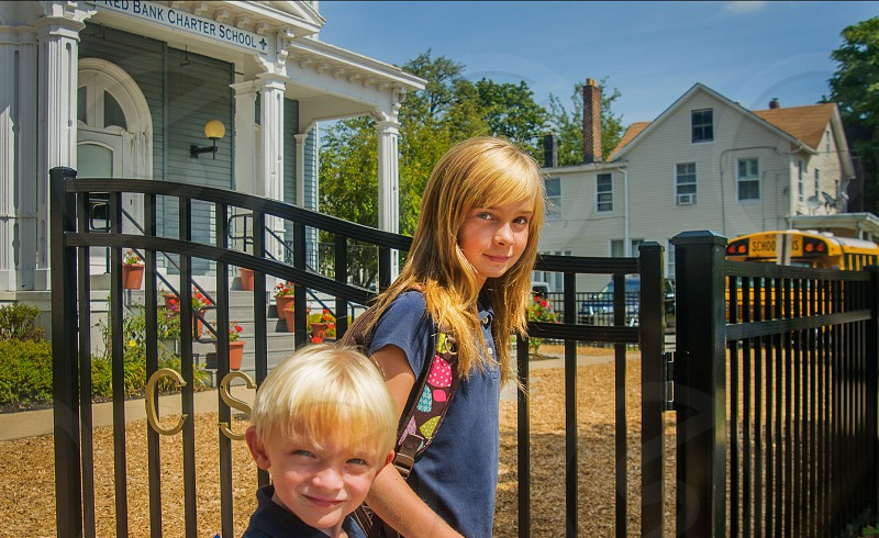 blonde haired boy and girl standing in front of open gate during daytime photo