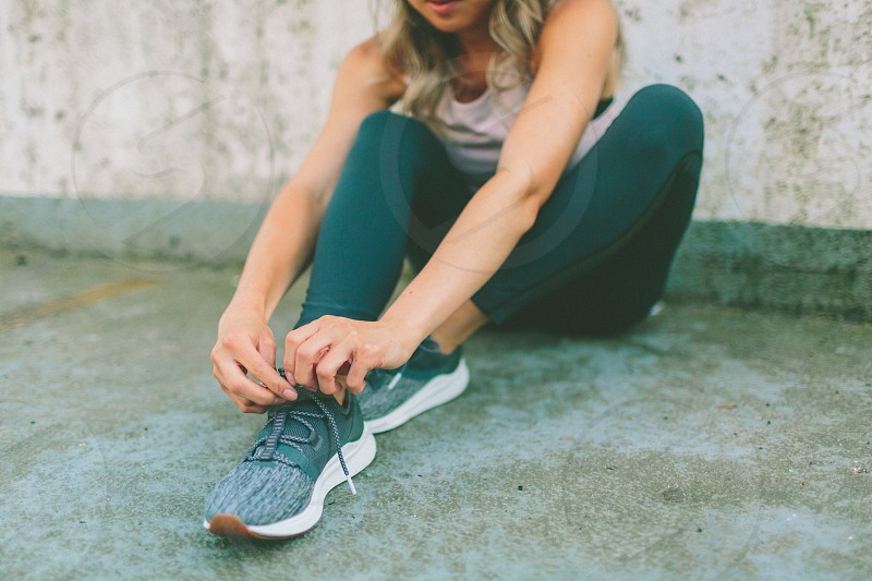 A woman tying her shoes before a workout. photo