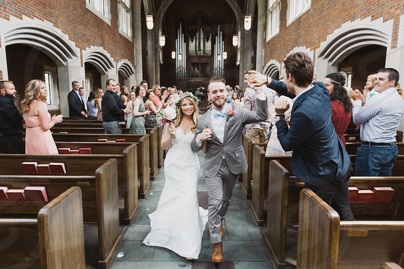 newly wedded couple marches down the aisle in the church with cheering people photo