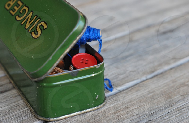 green singer metal container on a wooden surface photo