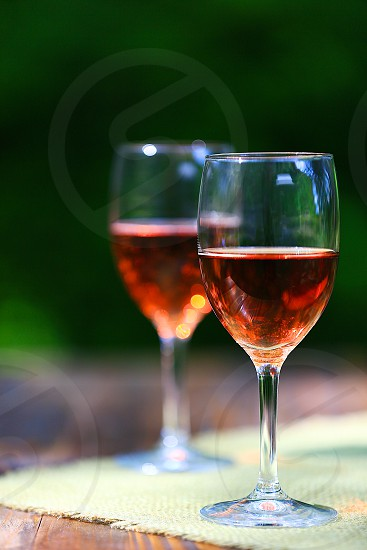 'Still life of Rosé Wines' (1) beverage Rosé Wines rose wine wine no branding pink hero shot wine glass rustic wood table rustic wood surface tablecloth bokeh outdoor natural daylight Summer feeling Summer tone greenery background trees background sun peeking through fruit strawberry copy space portrait vertically long longitudinally long DSLR camera photo