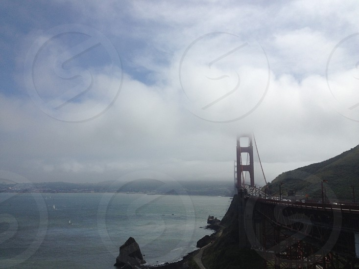 panoramic structural photography Golden Gate Bridge under white clouds on teal sky photo
