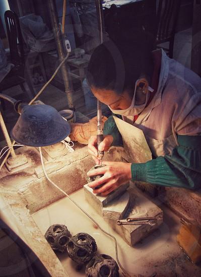 Chinese handicraft stone carver at work photo