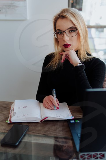 Young beautiful business woman looking seriously wearing glasses and writing notes photo