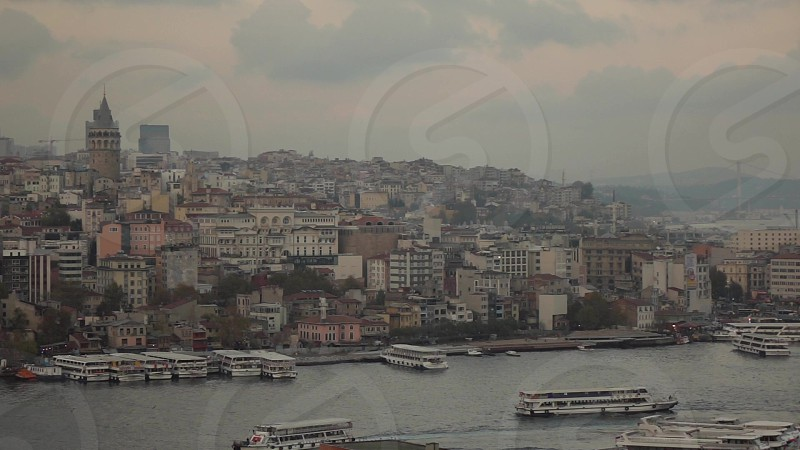 Beautiful cityscape of old part Istanbul with Galata Tower view to Golden Horn with travel ships and boards on a background of cloudy sunset sunny sky. Slow motion Full HD video 240fps 1080p. photo