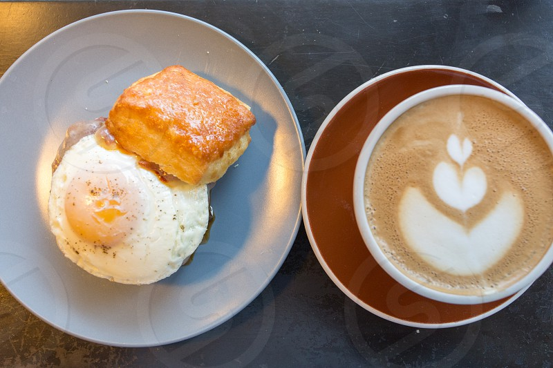 fried egg on gray ceramic round plate beside coffee with cream photo