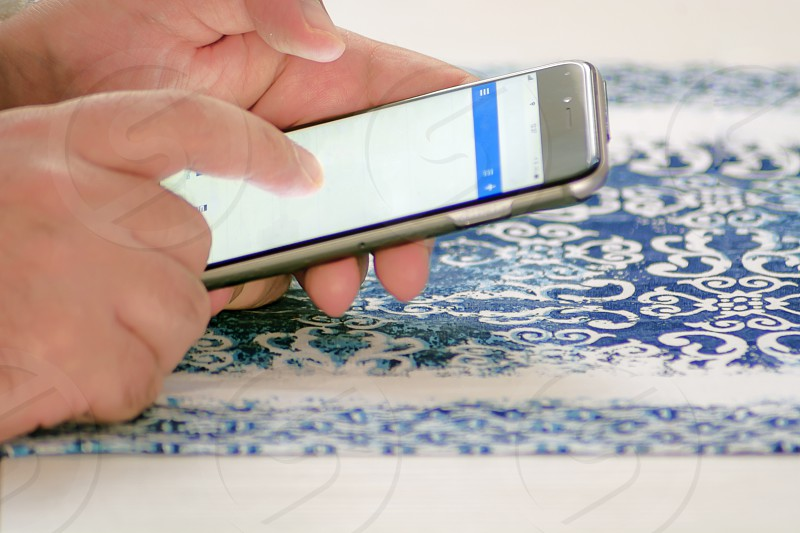 Male hand checking mail using a smartphone by touching the screen with fingers photo