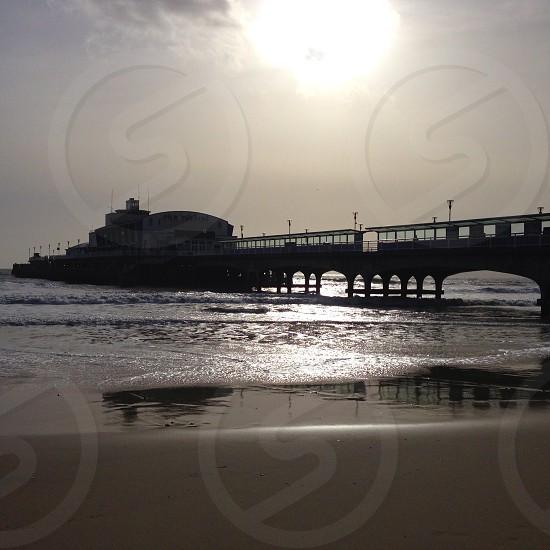 pier over body of water under gray sky photo