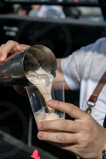 Bartender pouring fresh cocktail drink from metal shaker into plastic glass close up photo