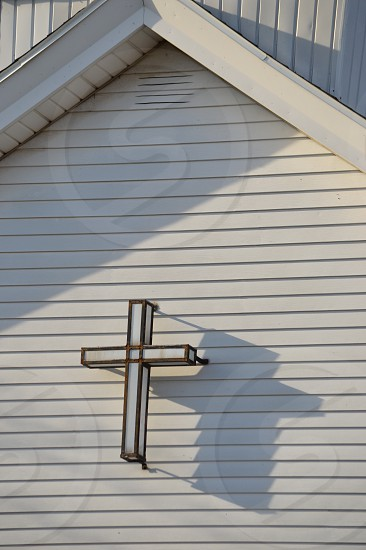 Stained glass cross on church with long shadows in the late day photo