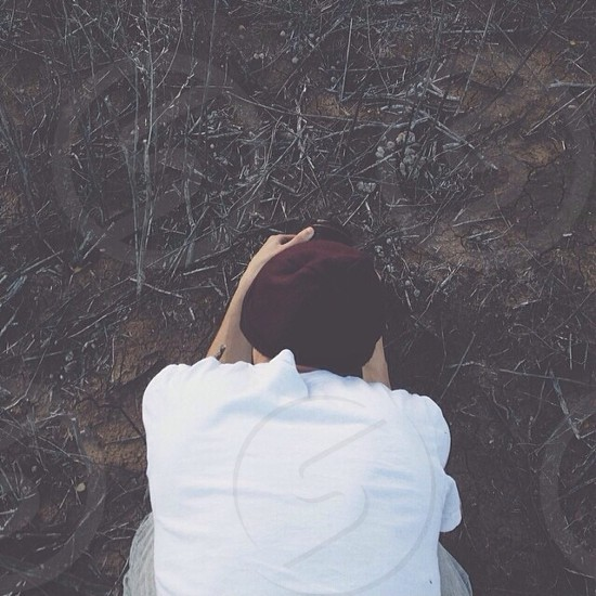 man wearing a white tshirt and black knit cap kneeling in the dirt photo