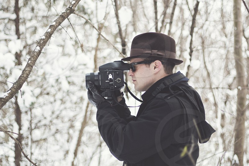 man taking picture using black dslr camera in the forest during winter photo