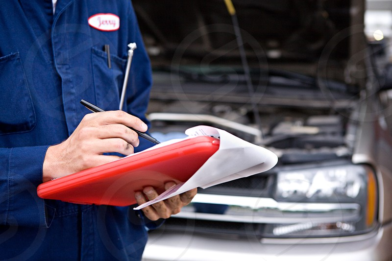 Mechanic Inspecting SUV With Clipboard  people; Caucasian; anonymous; holding; clipboard; writing; garage; truck; auto; vehicle; transportation; service; service industry; job; occupation; working; man; male; hood; suv photo