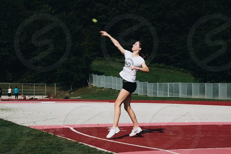 Girl throwing a tennis ball. photo