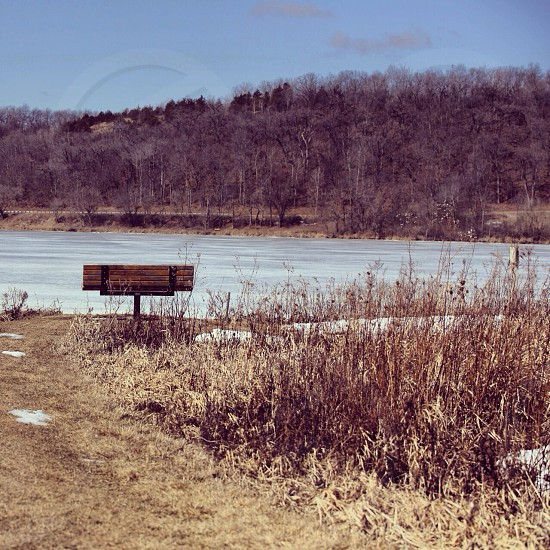black metallic framed brown wooden bench beside lake with brown grass around photograph photo