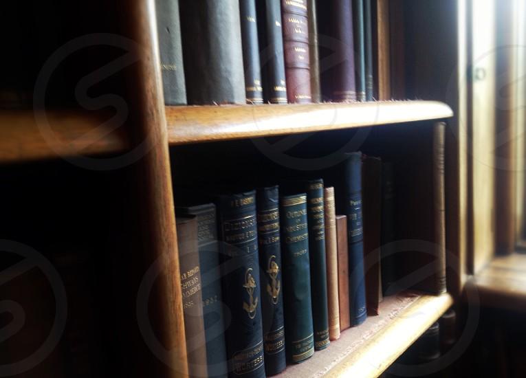 black hardbound books on brown wooden bookshelf photo