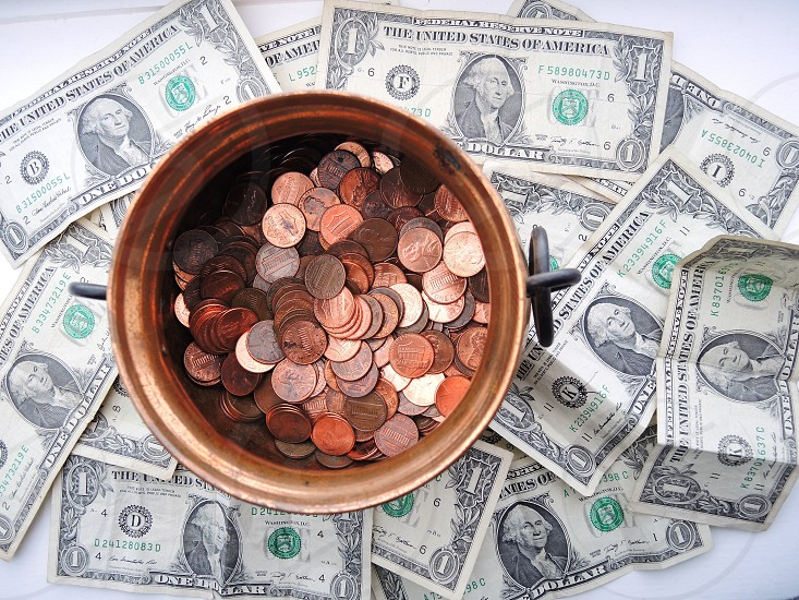 stacks of round coins on brass container on top of 1 u.s. dollar bills photo
