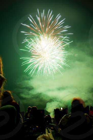 Green fireworks and crowd photo