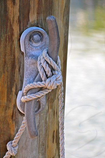 gray rope tied on metal rack attached on brown wall photo