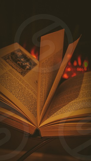 focus photo of open book on gray surface with a background of red fire photo