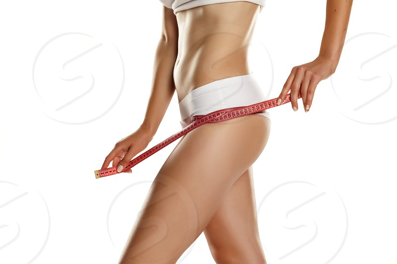 young slim woman measures her hips with measuring tape on white background photo