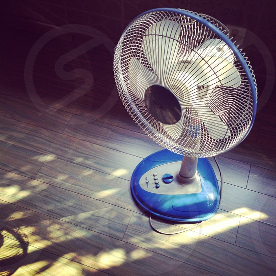 blue and white electric fan on brown floor photo