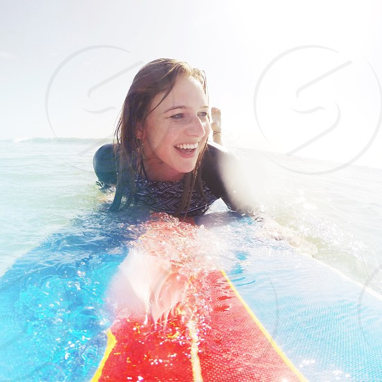 woman lying down on blue and red surf board waiting for the wave photo