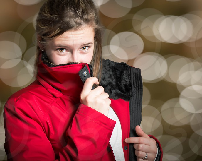 girl in red and black zip up jacket covering her mouth photo
