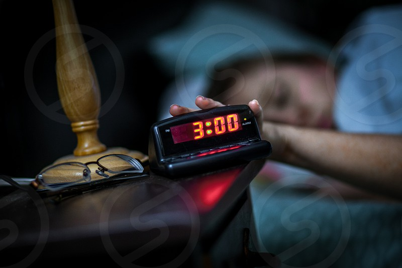 A woman's hand hits / turns off / slaps off a black plastic digital alarm clock on a nightstand with a photo / picture frame eye glasses and lamp.  Night 3:00 o'clock AM rings red numbers wood metal female girl lady fingers arm sleep wake early. photo
