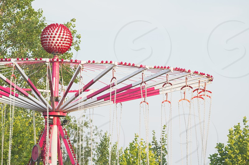 White and Red Carousel Top Closeup with Trees and Sky photo