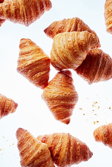 Pattern with floating homemade delicious freshly baked croissants on a light background. Concepr of continental breakfast. photo