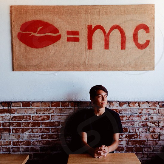 man sitting at table leaning the wall with mc coffee bean sign over head photo