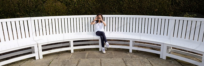 Panoramic portrait of a little girl sitting on a long white garden bench taking a photo on her mobile phone towards the camera wearing blue leggingswhite top and white trainers photo