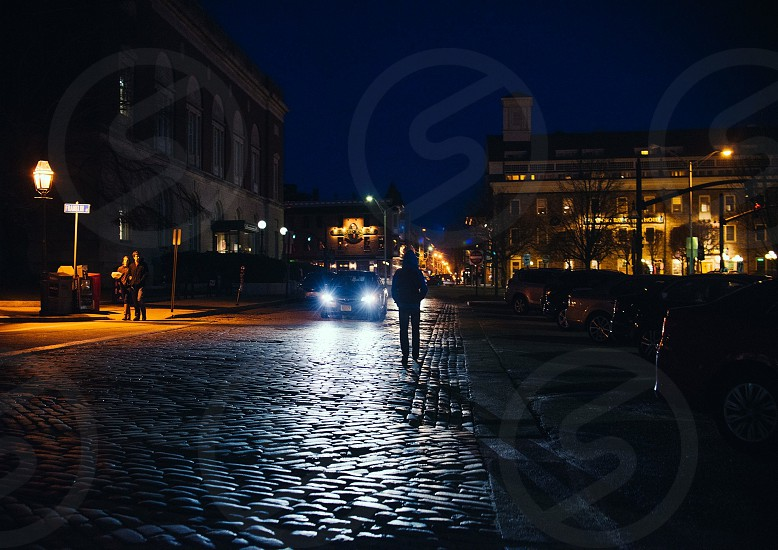 person standing on city street under night sky photo