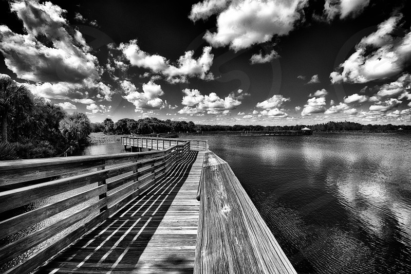 grayscale photo of wooden dock beside body of water under clouds photo